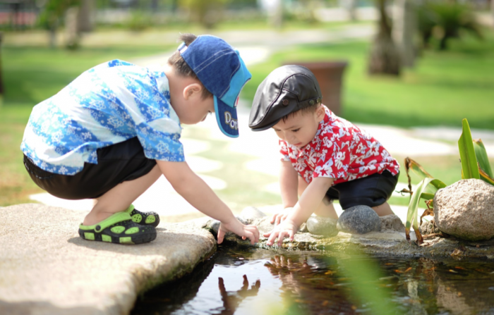 kids playing outside by a pond